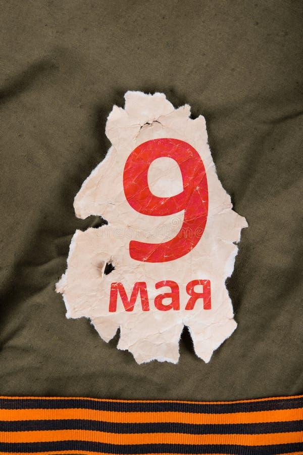 Datum 9 Mei op een blad, op de oppervlakte van militaire doek met stock afbeeldingen
