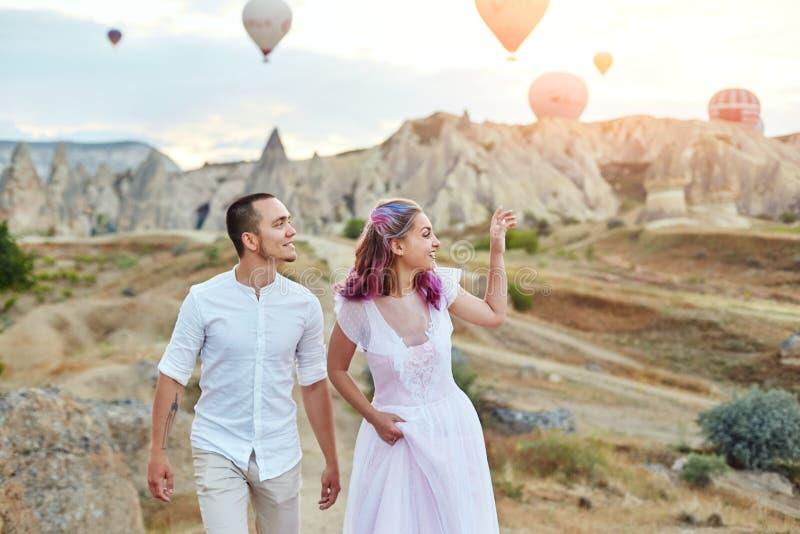 Datum van een paar in liefde bij zonsondergang tegen achtergrond van ballons in Cappadocia, Turkije Man en vrouwen koesteren die  royalty-vrije stock afbeelding