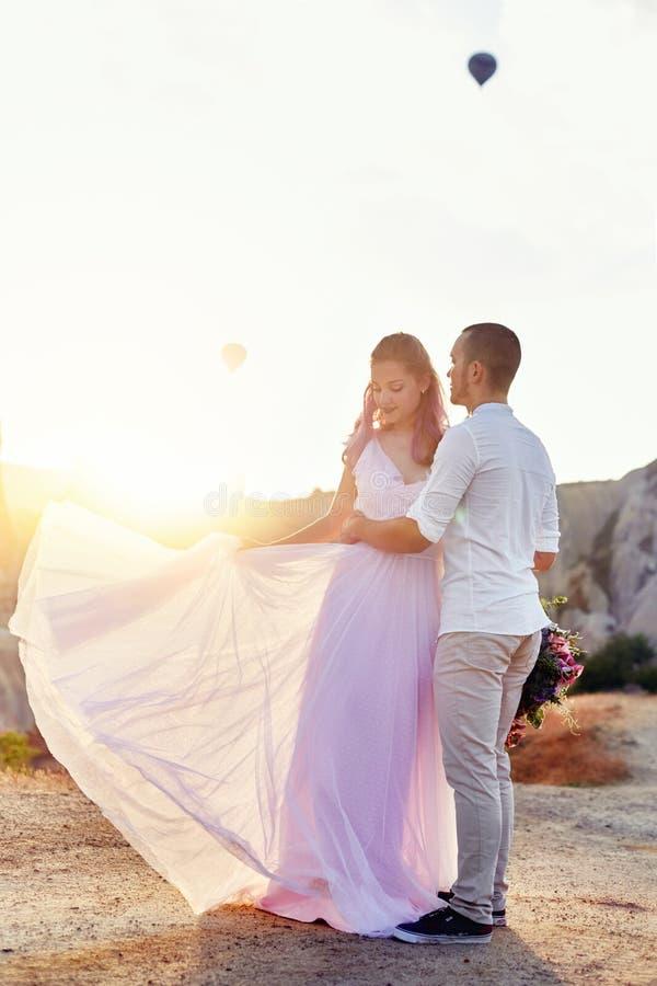 Datum van een paar in liefde bij zonsondergang tegen achtergrond van ballons in Cappadocia, Turkije Man en vrouwen koesteren die  stock fotografie