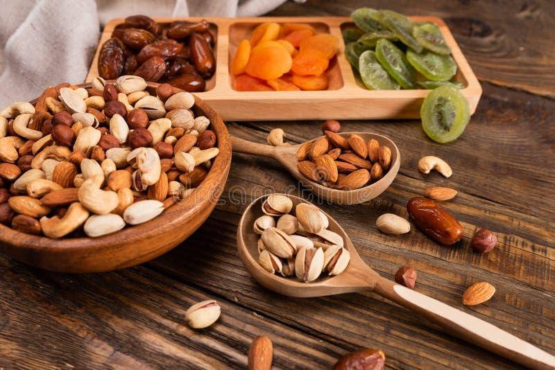 Daty, wysuszone morele i kiwi w, Compartmental asortymencie dokrętki w drewnianym pucharze na ciemnym drewnianym stole i naczyniu zdjęcia stock