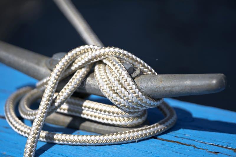 Dauerhafter Schiffstau ist Wunde an der Metallliegeplatzklammer, die am Rand des hölzernen Piers verstärkt wird lizenzfreie stockfotos