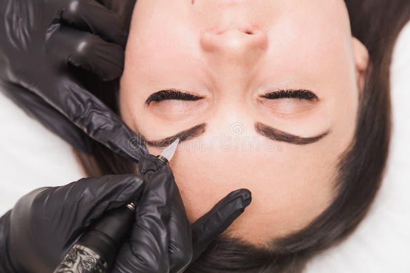 Dauerhaftes Make-up für Augenbrauen der schönen jungen Frau im Schönheitssalon lizenzfreies stockbild