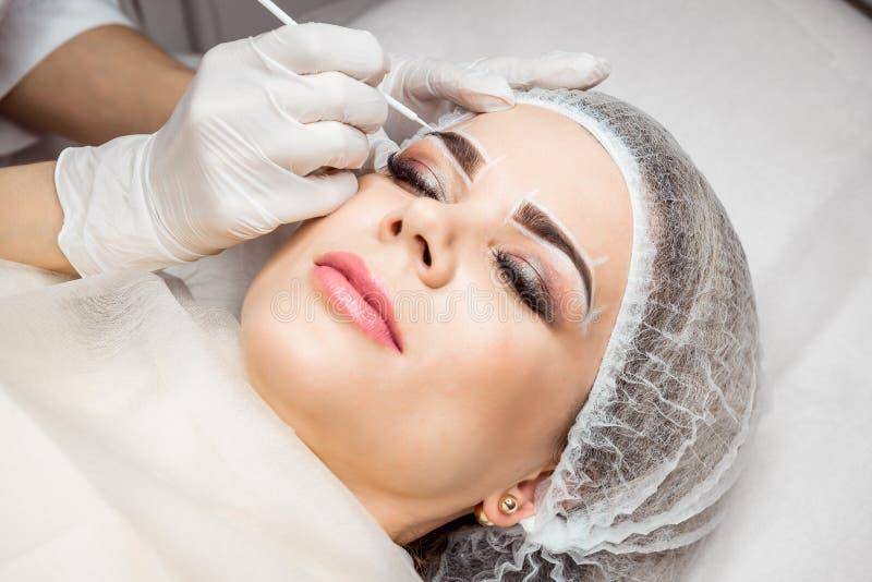 Dauerhaftes Make-up für Augenbrauen Nahaufnahme der Schönheit mit den starken Brauen im Schönheits-Salon Kosmetiker Doing Eyebrow lizenzfreie stockfotos