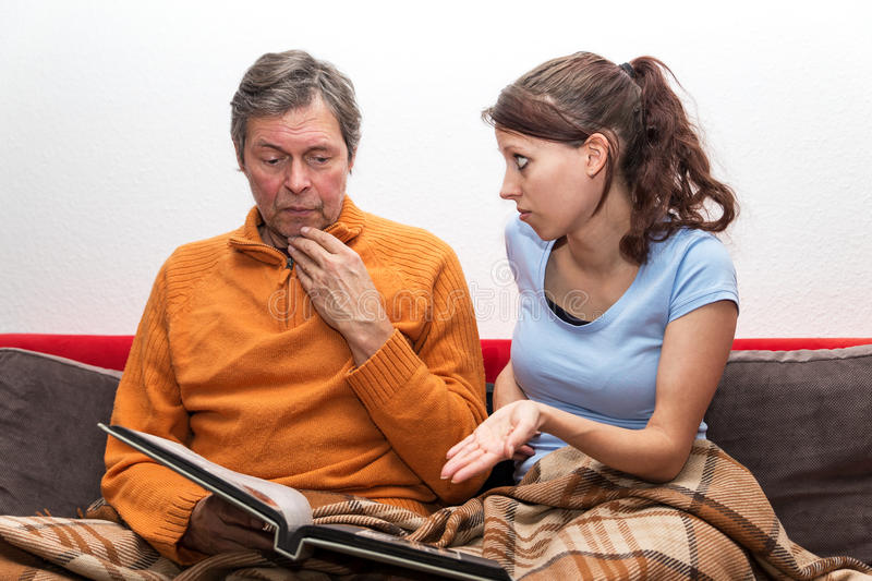 Daughter with alzheimer father. Daughter is trying to awake memories stock image