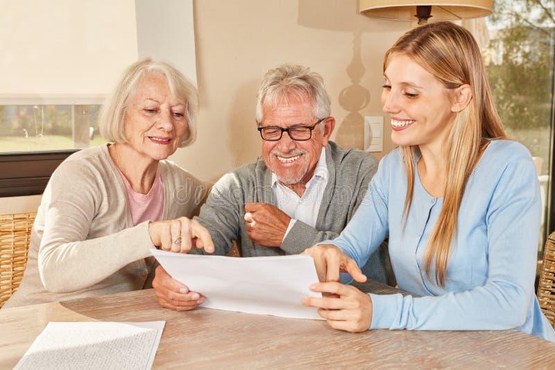Daughter helps seniors planning their retirement plans. Daughter as a consultant helps senior couple planning their retirement stock photo