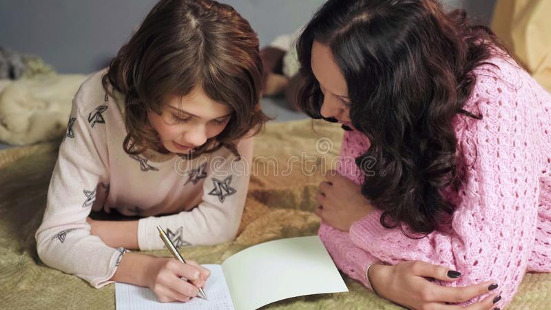 Daughter attentively doing homework, mother monitoring mistakes, home education royalty free stock images