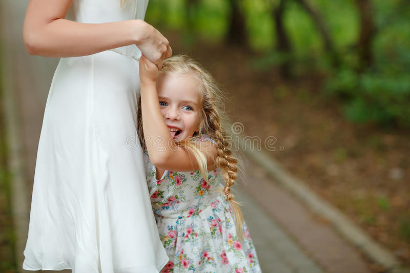 Daughter blonde summer sunset hugs mother and laughs royalty free stock photography