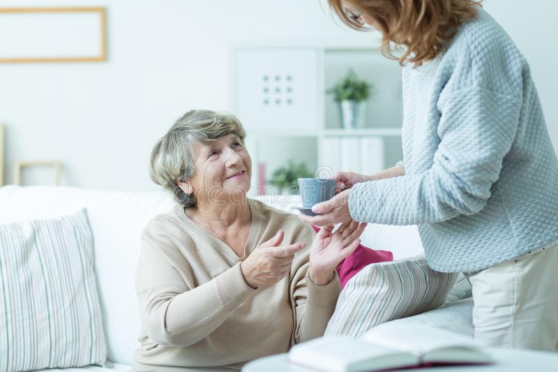 Daughter caring about elder mother stock photo