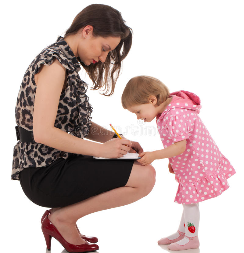 Daughter is checking mom's organizer. Business lady is writing something into organizer book and her daughter is checking and trying to find when mom is royalty free stock photos