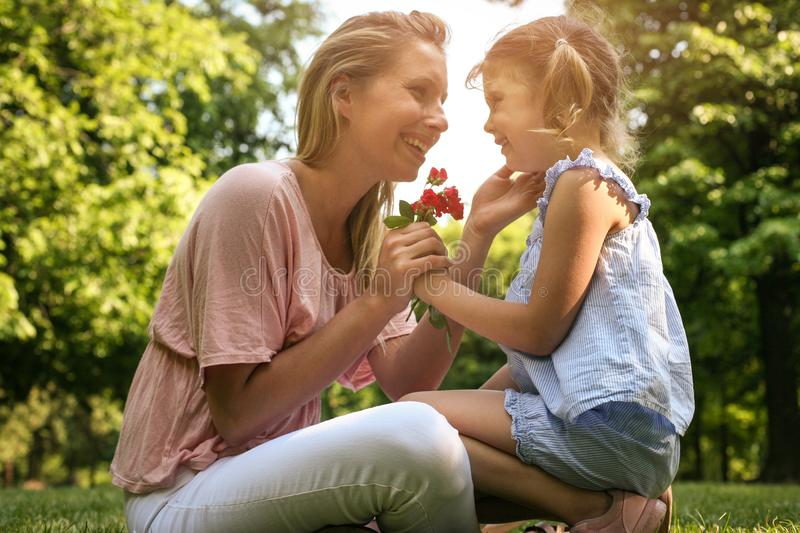 Daughter chose a flower to his mother. Girl gives mother to smell a flower that was plucked. Lifestyle stock photo