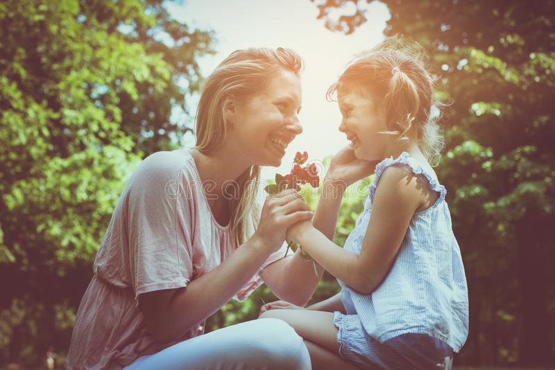 Daughter chose a flower to his mother. Girl gives mother to smell a flower that was plucked stock images