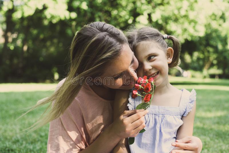 Daughter chose a flower to his mother. Girl gives mother to smell a flower that was plucked stock photo