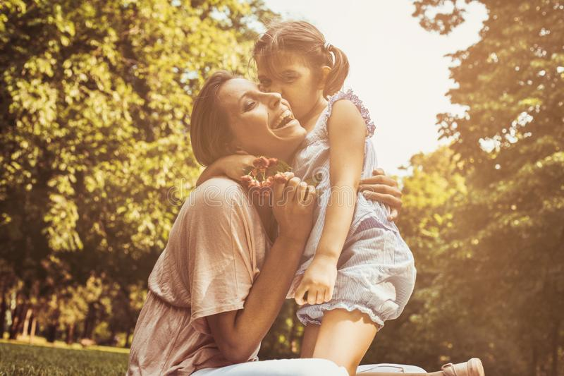 Daughter chose a flower to his mother. Girl gives mother to smell a flower that was plucked. Lifestyle stock photography