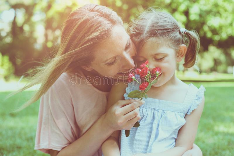 Daughter chose a flower to his mother. Girl gives mother to smell a flower that was plucked. Lifestyle royalty free stock photos