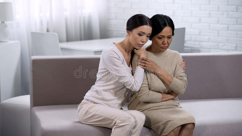 Daughter consoling mother, saying supportive word, giving advice about relations royalty free stock photography