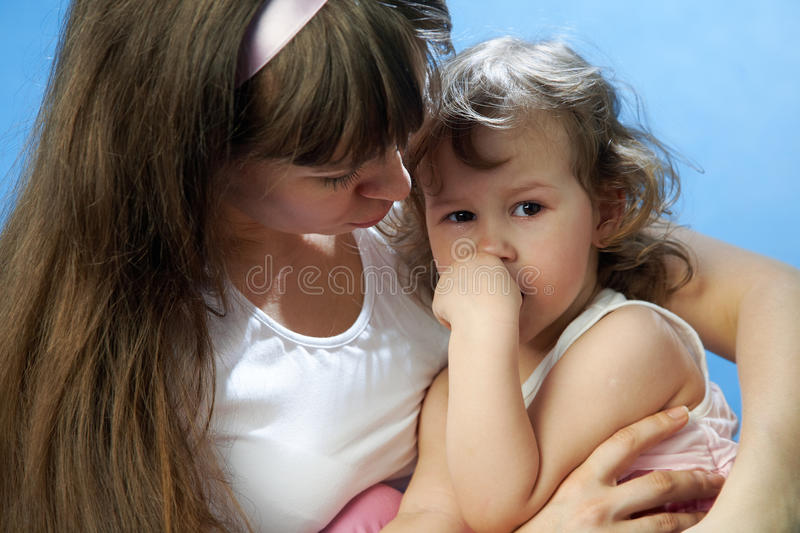 Daughter crying in the arms of mother stock image