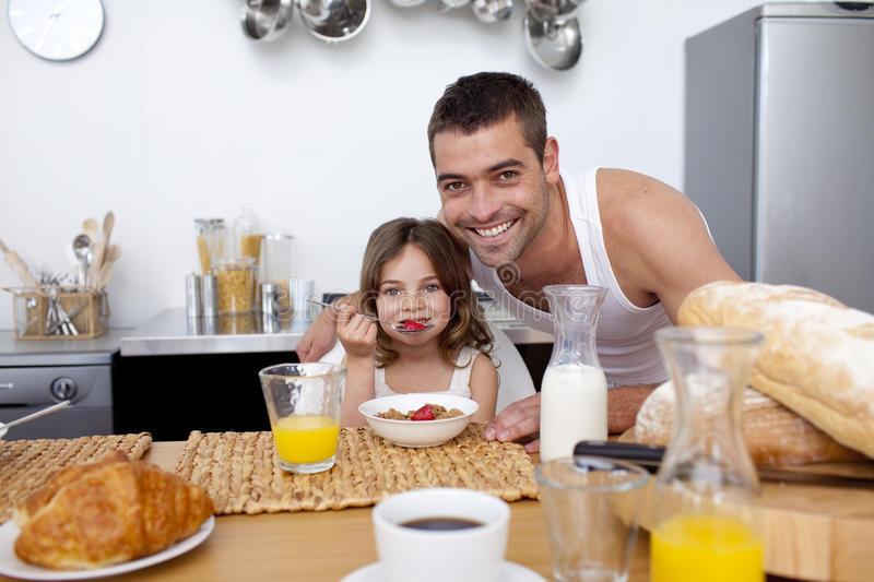 Daughter eating cereals and fruit in kitchen royalty free stock photography