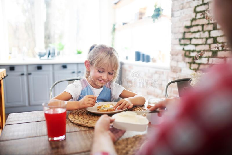 Daughter eating yummy toast with egg in the morning royalty free stock image