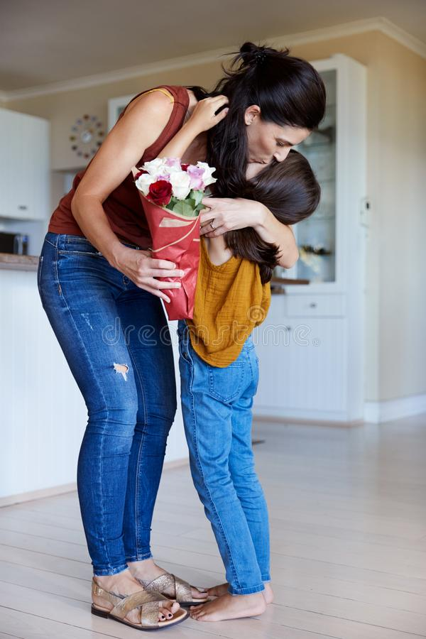 Daughter embracing her mother after giving her flowers on her birthday, full length, vertical stock photography