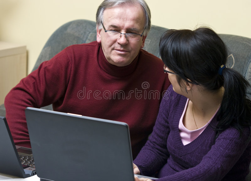 Daughter and father. With laptops sitting and talking royalty free stock photography