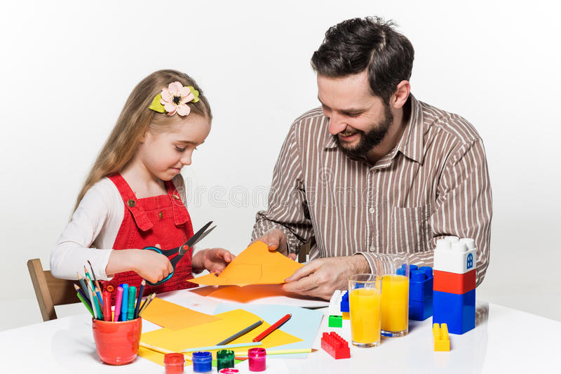 The daughter and father carving out paper applications. Together on white background stock photography