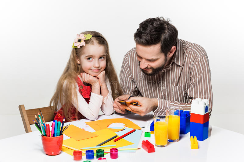 The daughter and father carving out paper applications. Together on white background stock images