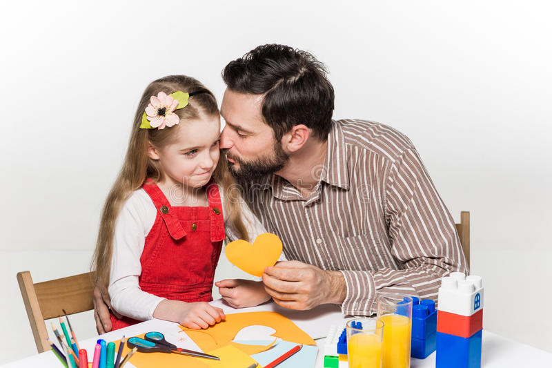 The daughter and father carving out paper applications. Together on white background stock image