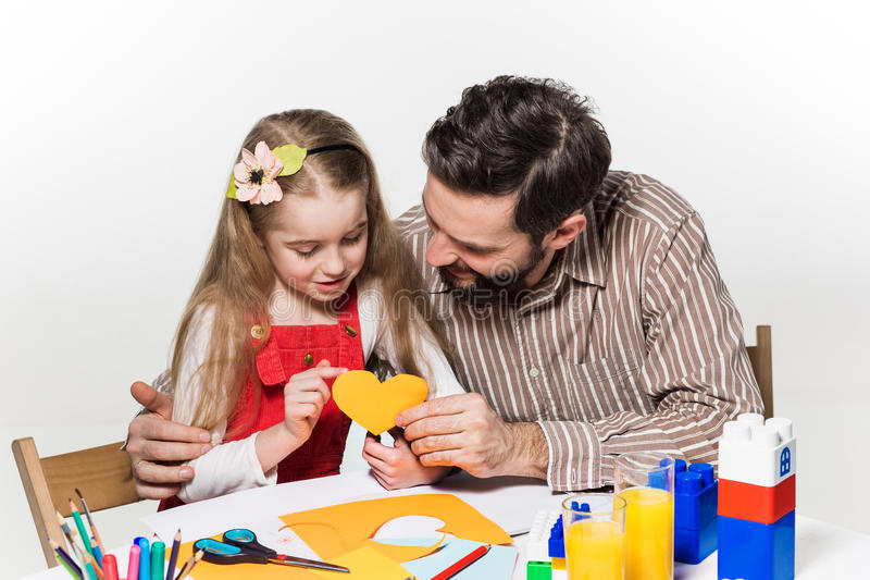 The daughter and father carving out paper applications. Together on white background royalty free stock image