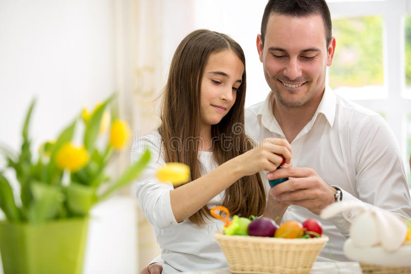 Daughter and father having fun with Easter eggs stock image