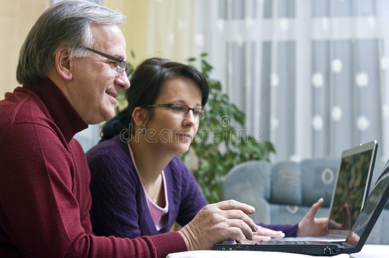 Daughter and father on laptops. Daughter and father working together on laptops royalty free stock photos