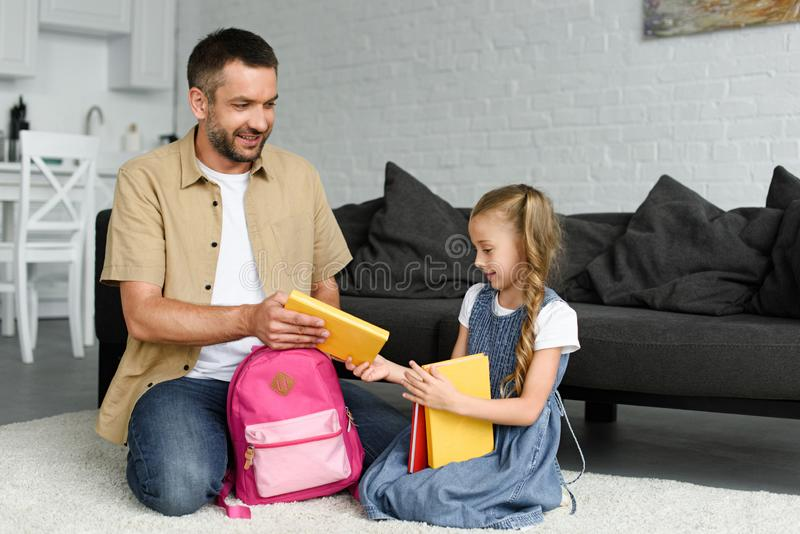 Daughter and father packing backpack for first day at school back to. School concept royalty free stock images