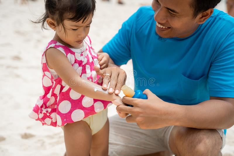 A daughter feels strange when father rubbing a sunblock to his arm. Before playing around the beach stock photography