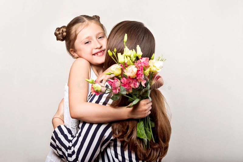 Daughter gives flowers to her mother on her mother`s day.  stock photos