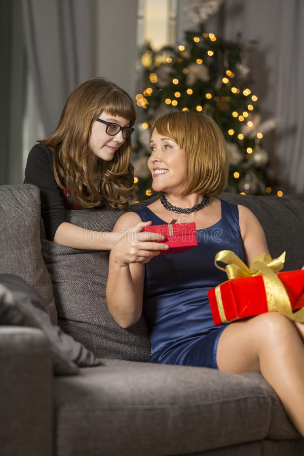 Daughter giving Christmas present to mother at home stock image