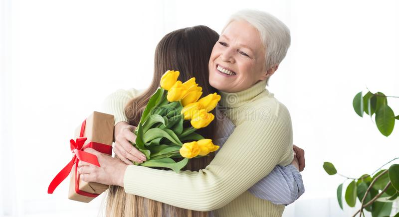 Daughter giving flowers and present to her mother stock photo