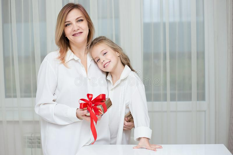 Daughter giving her mother a christmas present royalty free stock photo