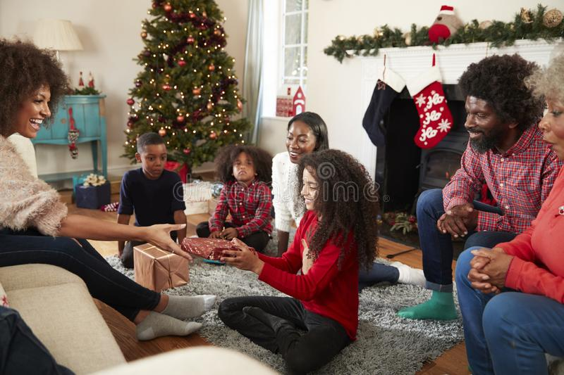 Daughter Giving Mother Gift As Multi Generation Family Celebrate Christmas At Home Together royalty free stock photo