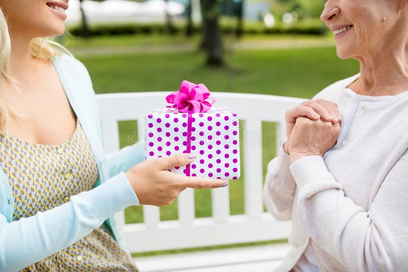 Daughter giving present to senior mother at park royalty free stock image