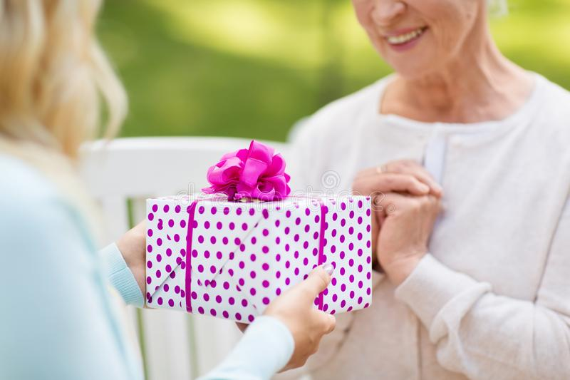 Daughter giving present to senior mother at park royalty free stock photos