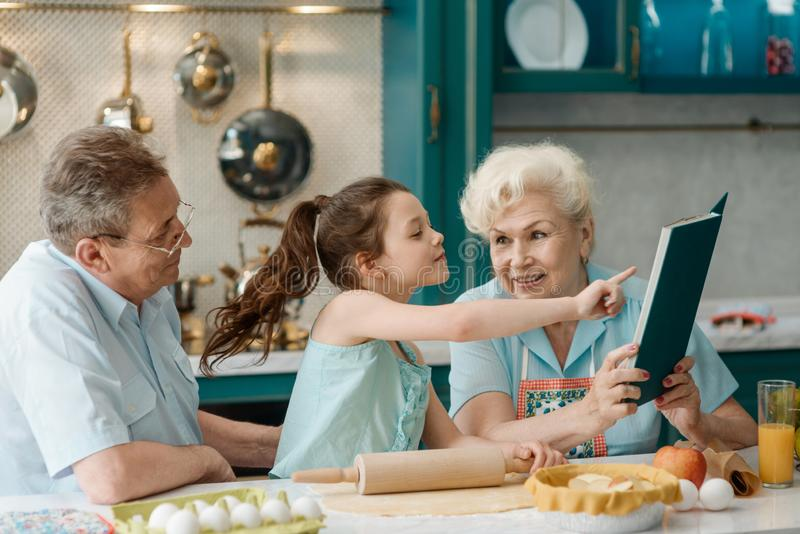 Daughter and grandparents baking together stock photos