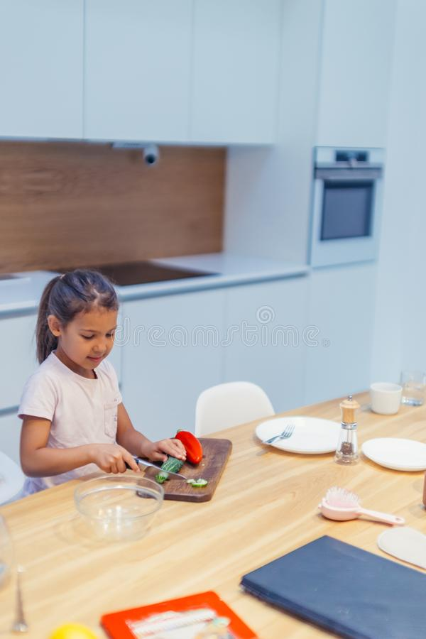 Little girl cooking, help mother to cook at home royalty free stock image