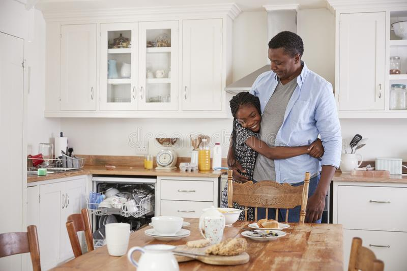 Daughter Helping Father To Clear Table After Family Meal stock photos