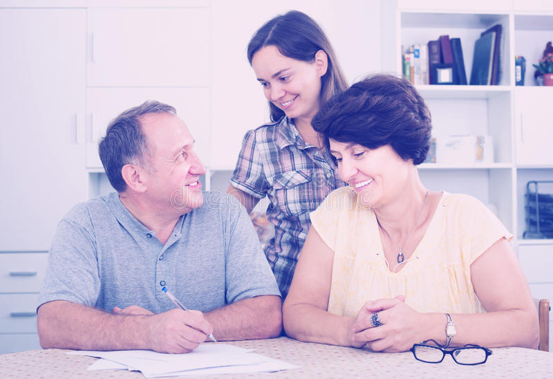 Daughter helping her senior parents to do paperwork. Young women daughter helping her senior parents to do paperwork at home royalty free stock photo