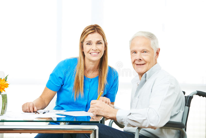 Daughter helping senior man with contract. Daughter helping senior men in wheelchair with contract at home stock photography