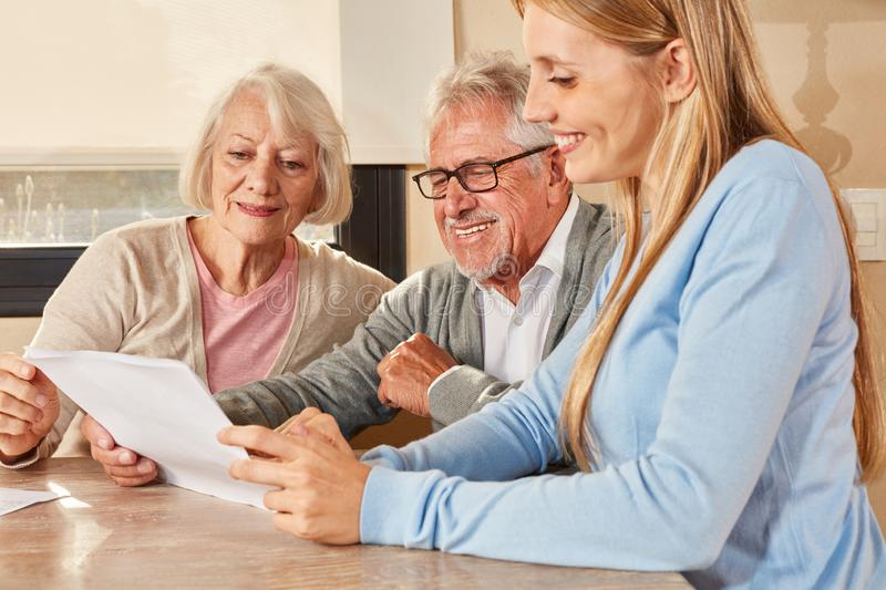 Daughter helps the elderly with insurance and pension royalty free stock photography
