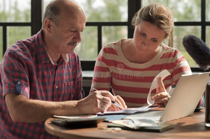 Daughter helps her father count money and manage the family budget. Senior men looking on bills and taxes royalty free stock photo