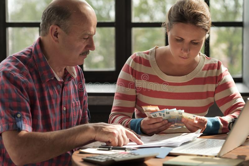 Daughter helps her father count money and manage the family budget. Senior men looking on bills and taxes stock image