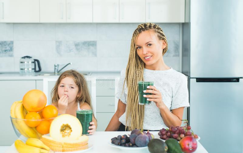 Daughter and her happy mother drinks green smoothie. Vegan meal and detox menu. Mother and daughter drinking green royalty free stock photo