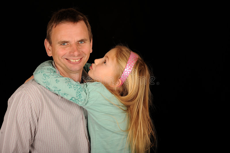 Daughter hugging father stock photography