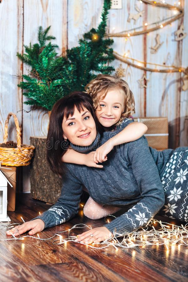 Daughter hugs mom lying on the floor against the backdrop of New Year`s scenery, next glowing lights royalty free stock images
